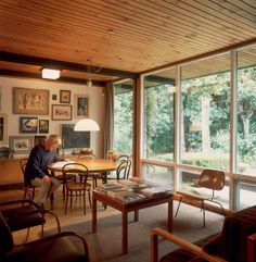 Bill Alington, architect, in the dining area, in which he lowered the height of the dining table and the window transoms to create a sense of greater spaciousness. The 'Brno' chairs by Mies van der Rohe at left are a reminder of the architect who inspired the home's design. The sofa in the foreground is by Ernst Plischke, and the 'LCM' plywood chair is by Charles and Ray Eames.