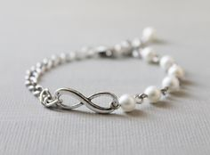 Bridesmaids gifts for a Toy Story themed wedding -- Infinity Bracelet. antique silver infinity ring with czech glass pearl beads. $18.00, via Etsy.
