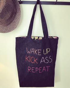 """I made this embroidered tote bag from some black denim, lined with a patchwork fabric with sugar skulls. It was a bit plain so I embroidered """"Wake up, kick ass, repeat"""" to give it some attitude."""
