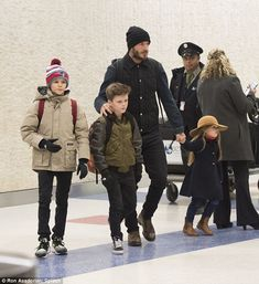 Watchful eye: David kept his children close as they made their way thorough the terminal