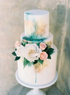 Green and gold wedding cake with roses and geometric details