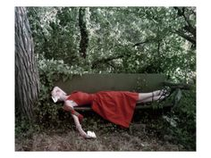 Vogue - January 1948    A model lounges on a bench, surrounded by woods, in this John Rawlings photograph, which appeared in the January 1, 1948, Vogue. She wears a full-skirted red dress and striped scarf. The outdoors lends this work a relaxed atmosphere, while the burst of red gives it a certain energy.