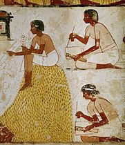Scribes with reed pens and papyrus sheets measuring
