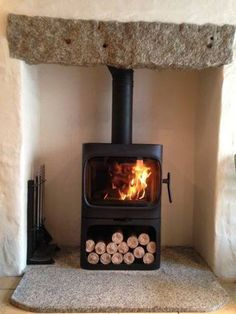 Freestanding Woodburning Stove-Jotul 305 B--I love the wood storage underneath the stove! See our website for more beautiful stoves like this: http://jotul.com/us/products/stoves