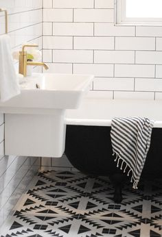 Black-and-white patterned cement tile that was inspired by traditional quilting blocks creates a bold statement in this small, efficient urban bathroom. | Via Curbly