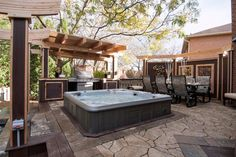 An intricate arched shade structure and outdoor kitchen play back up to the centerpiece of this al fresco space—a party-sized hot tub.