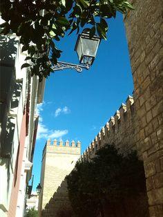 Murallas Reales (Sevilla) - Vista de la calle Joaquín Romero Murube desde la Plaza del Triunfo, en la que se observa parte de las murallas de los Reales Alcázares.