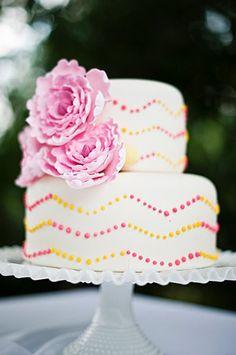 Torta decorada con rayas chevron de colores rosa y amarillo.