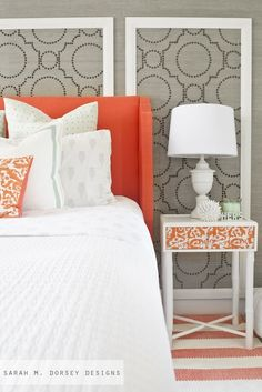 Fabulous orange and gray bedroom with gray grasscloth wallpaper, Sherwin-Williams Coastal Cool Wallpaper Collection, accented with brass nailhead trim framing orange wingback headboard.