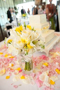 Yellow, white and green bridal bouquet with pink rose petals and wedding cake, photo by Adam Nyholt