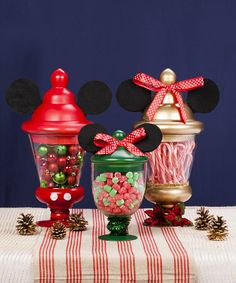 """Make Mickey and Minnie the center of your holiday table by adding the iconic ears and a little Christmas décor to simple pedestal jars. Fill them with candy so they become a sweet treat for your friends and family. Get guests involved at your next holiday party by using your centerpiece as a fun """"guess how many candies are in the jar"""" game."""
