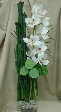 This is an arrangement featuring white cymbidium orchids. See our entire…