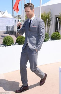 Suited and booted: The actor paired his grey suit with a white shirt, dark blue tie with small white spotted pattern, matching blue socks and shiny red-brown dress shoes