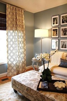 Sage green walls, white baseboards, ceiling to floor drapes, simple floor lamp, symmetrical/uniform display of B photos in simple black frames w/white mats.