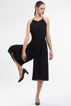 IDYLLIC CULOTTE JUMPSUIT by PULSE Made from breathable triple veil, with an open-back that reveals a subtle sliver of skin and then extending into loose shorts, this black jumpsuit is a flattering and easy-to-wear piece. It's finished with a keyhole back and zipperin back. Material: Triple Veil 65% Polyester 35% Viscose Colour: Black Size: EU 34 - US 2 to EU 44 - US 12 Care: Dry clean.