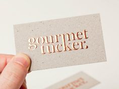 Gourmet Tucker business card with copper block foil print finish across a mixed fibre, uncoated, unbleached board designed by Supply.
