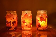 Mason jars with leaves around the outside and a candle in it