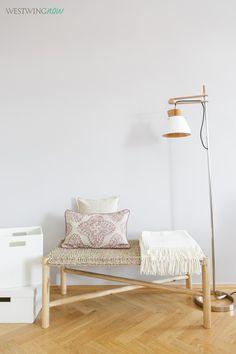 Die Holzbank aus geflochtenem Seegras lässt vom Wilden Westen träumen. Den coolen Kontrast liefert die schlichte Stehleuchte im typischen Skandi-Format.