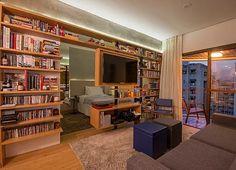 Sala de estar integrada com quarto. Estante de madeira vazada com livros, discos, CDs e DVDs com TV giratória. Viga em concreto aparente iluminada com fita de LED