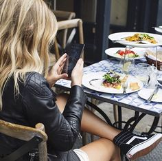 She eats with her legs crossed, sneakers loose and hair wavy.