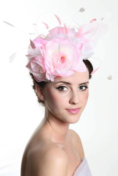 Chatto. A white sinamay button cap, covered in pink and white swirls of silk organza, with stripped feathers and fine silk flowers.