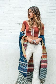 The textured lace bell bottom pants combined with the patterned wrap are both classic elements of the boho style. Photography via Rocky Barnes. The pants are from Made for Pearl, top from Free People, wrap from Lovestitch and the necklace is from Ax