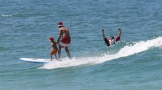 A man and his son surf past Santa at Burleigh Heads, Queensland. (Image: Damien Larkins/ABC)