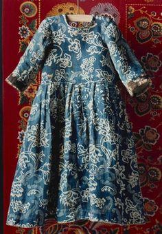 DigitaltMuseum - Barnkolt i blåtryck, sekelskiftet 1700-1800, i bakrunden rödbottnad kattun från schweiziskt tygtryckeri. Nordiska museets föremål inv.nr 3206.