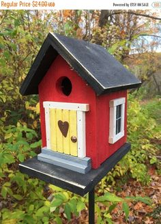 This birdhouse measures approx. 6 wide by 6 1/2 deep by 8 1/2 tall. It has been painted red and has a black roof and base. Two windows on each side are framed in white trim. The hand grooved yellow door is also framed in white trim. A 1 1/2 rusty primitive star and upholstery tack door knob make this little nesting house a cozy place for small songbirds.  The entry hole is 1 1/4 with a rusty nail perch. There are two well worn steps that lead up to the door. The birdhouse has been given a…