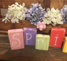 These rustic Wood Spring blocks are sure to brighten any room and will look adorable displayed on a mantle or as a table centerpiece! This cheerful Spring sign is hand painted in vibrant spring colors and have been hand lettered (no vinyl or stencils used). Three of the blocks have handmade wood cutouts (dragonfly, butterfly and flower) suspended on black twisted wire and give such a cute effect to this sign! (Photo props not included).  This decoration is made from 2x4 wood and heights vary…