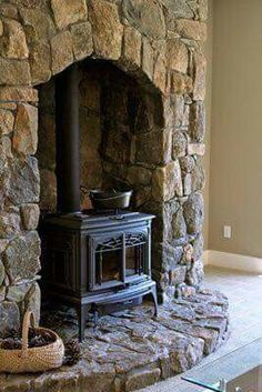 """wood burning stove fireplace with chimney surround except I would add stone """"bench"""" on either side and a hearth This free-standing wood stove inside a stone fireplace by Smith and Robertson Custom Building and Design would give extra charm to any Wood Stove Surround, Wood Stove Hearth, Stove Fireplace, Wood Burner, Fireplace Design, Wood Stove Wall, Stone Wall Fireplaces, Corner Wood Stove, Craftsman Fireplace"""