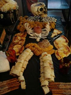 """Autopsy table.  Everything but the skull head and red cups was edible.  Foods were served directly on the black plastic table cloth. Brain and heart were jello molds with fruit cooli. Stomach was also a jello mild with a cheese ball,  arms were home made pizza,  """"skin"""" by the neck were pumpkin pie cookies,  eyes were Nilla wafers dipped in white chocolate,  legs were roll ups, fingers were pickles and olives and rib cage is piped merengue."""