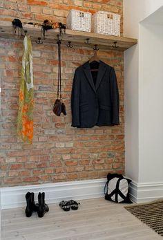 Estante colgante de madera, mas pared de ladrillo, y un espacio para las cosas que  nos sacamos no bien llegamos a casa.