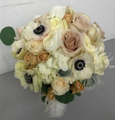 Bridal bouquet featuring hydrangea, anemones, roses, spray roses, ranunculus, silver dollar eucalyptus, and feathers by Studio AG