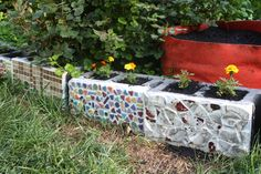 Cinderblock mosaics done with broken dishes and tiles. Portulaca & marigolds planted along edge of back garden. (5-13)