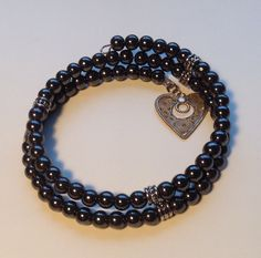 Black beaded bracelet with a heart charm. by LadyofAlbionArt
