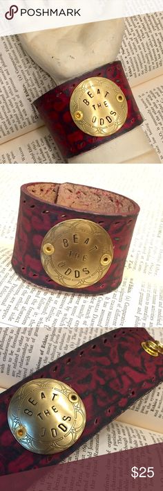 Handmade Wide Embossed Red Leather Cuff Beat the Odds  This red leather cuff has a handstamped brass colored medallion to serve as a reminder when you need a little courage. Originally created for a friend battling cancer, this saying could easily apply to other challenging situations as well.  Each of these bracelets is hand made and one of a kind. Any imperfections add to the handmade nature of the piece. These make great gifts!   The snaps are set to accommodate most wrists. I can attach…
