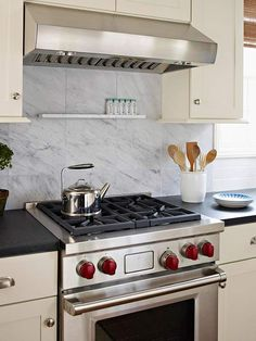Luxury on a Budget. Spice shelf, easy access for cooking. Marble on the range backsplash amplifies this kitchen's luxurious look. If you love marble, get the look for less by using marble tiles instead of a single marble slab.