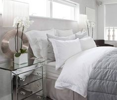 White and gray bedroom. Mirrored side table