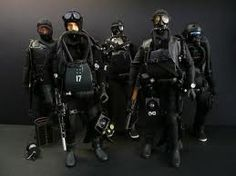 Navy SEALs in full dive gear with dry suits & rebreathers.  SEALs use rebreathers instead of SCUBA tanks not only because they are lighter and less bulky, but because they don't emit bubbles that float to the surface that could alert enemies to their presence below the surface.