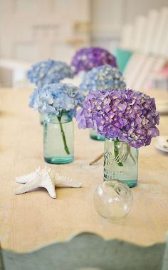 Table decor: beautiful blue and purple hydrangeas in soothing sea glass jars!