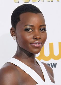"""Pin for Later: 40 Reasons Lupita Nyong'o Deserves the Title """"Most Beautiful"""" Critics' Choice Awards Lupita wore a faux widow's peak on the Critics' Choice Awards red carpet that directed the eye right down to her silvery grey eye makeup."""