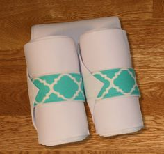 "Equine Standing Wraps/White Standing Wraps w/Teal Quatrefoil Velcro Straps. Made of White stretch polyester that is comparable to the stable bandages from Dover Saddlery. Made with industrial strength Velcro to ensure a strong hold.  Sold in Set of 4 Wraps. Two sizes offered: Pony: 2 yards (6ft) long, 5"" wide or Horse: 4 Yards (12 ft) long, 5"" wide"