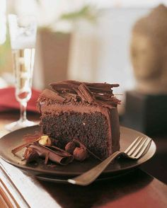 This luscious chocolate-hazelnut cake is coated with a ganache made from chocolate and cream. It's topped with a mountain of bittersweet chocolate curls, and surrounded by crunchy praline hazelnuts coated in tempered chocolate and rolled in cocoa powder.