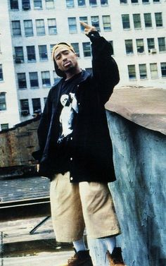 Tupac, wearing a t-shirt with a picture of himself giving the middle finger, giving the middle finger.
