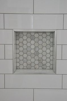 Looking to upgrade your bathroom shower? See how we used elongated white subway tile with dark gray grout and marble hex tile niche. Looks super luxe but on a budget! Click through for all the details.