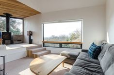 """晴れて雲の少ない日には、敷地の北端部分につくられたリビングの開口から富士山の雄大な姿が望める。このソファは富士山と相模湾の両方を見ることのできるM邸の""""特等席""""。"""