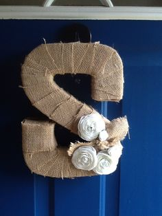 Cardboard letter wrapped with burlap.