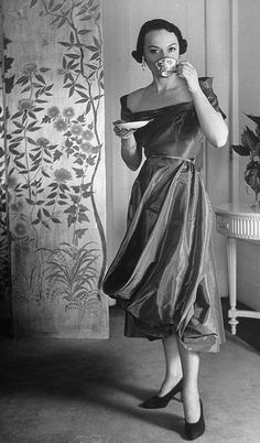1950    Model is wearing a high fashioned cocktail dress designed by Ceil Chapman