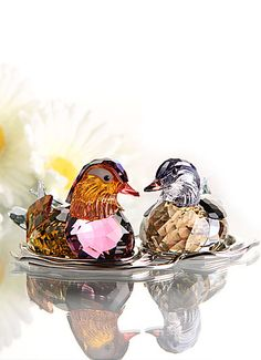 "Swarovski Mandarin Ducks, Topaz   $860.00 	6 1/4"" 		  Item# 1141631 	  	  	     Known for forming life-long partnerships, Mandarin ducks are a powerful symbol of long-lasting love and togetherness. The male's striking plumage sparkles in a stunning combination of rich crystal colors, including Topaz, Amethyst, and Indian Sapphire crystal. Inspired by the waves on the surface of a pond, the silver-tone metal display is not attached to the ducks, allowing you to place them in different…"